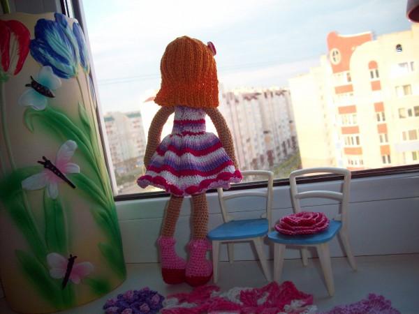 Милена стоит и смотрит в окно